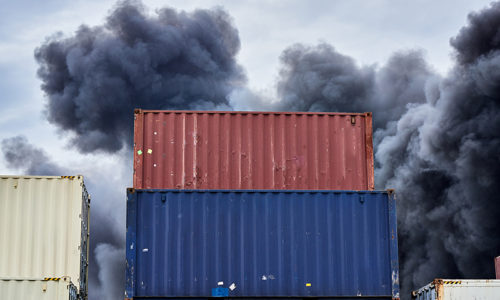 Shipping containers stacked in storage with plumes of black toxi